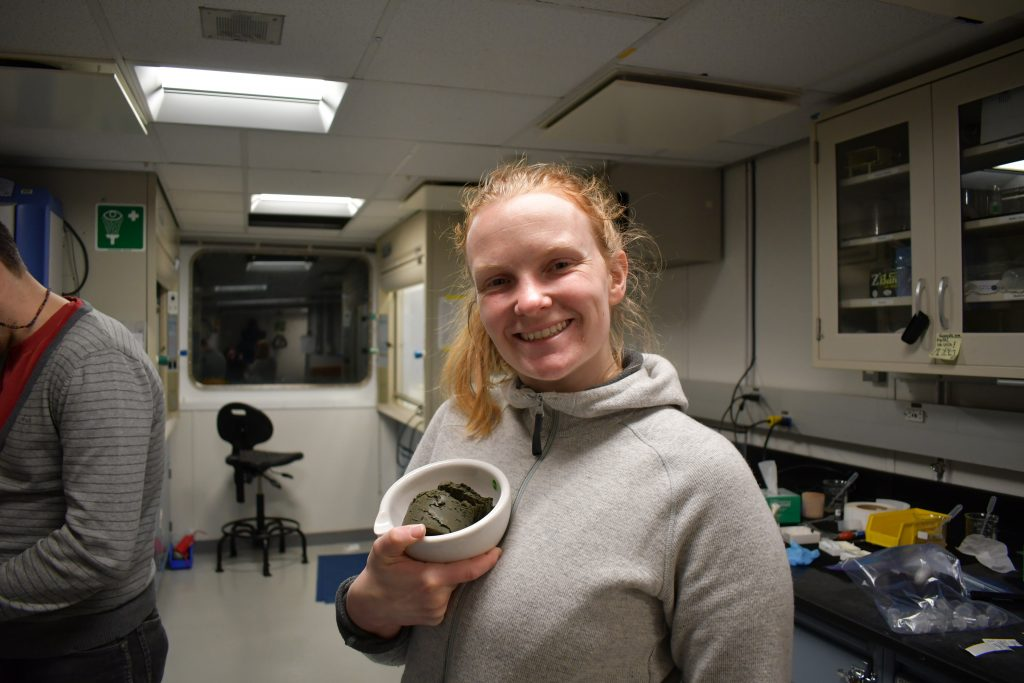 Smiling woman holding a bowl filled with grey mud.