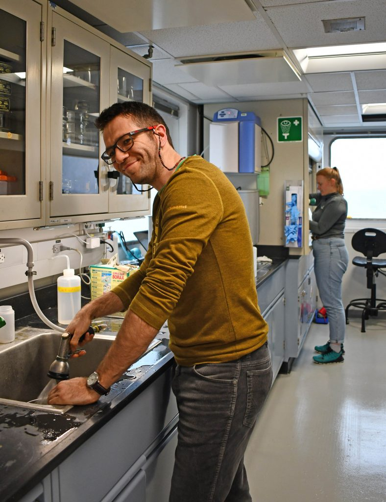 A smiling man washes sediment in a sieve in a laboratory