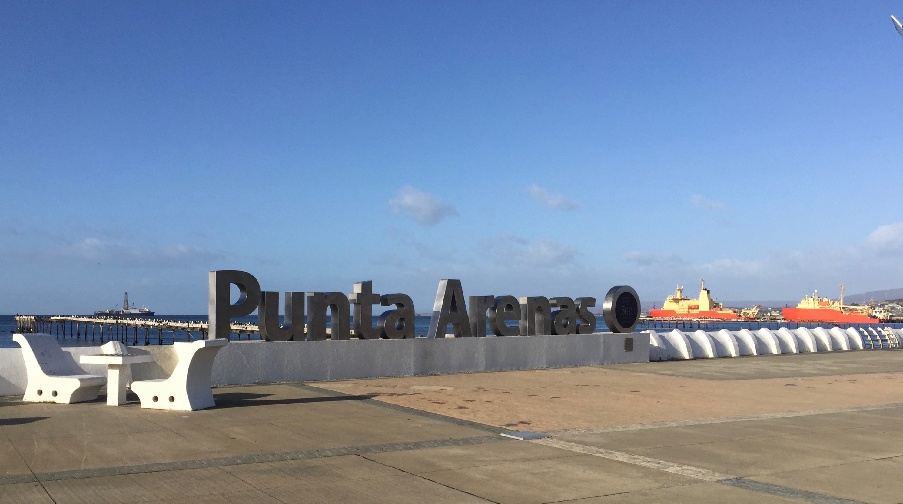 Three ships at anchor with the Punta Arenas sign in the foreground