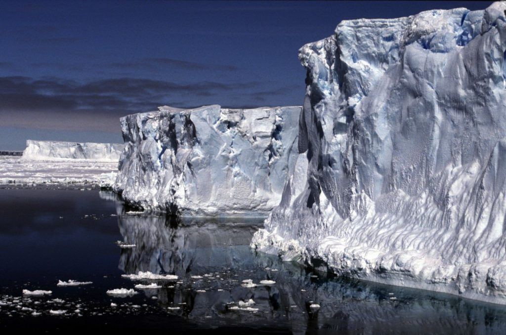 Ice shelf towering above dark, calm water