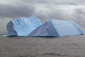 A blue iceberg. split down the middle, against a cloud sky