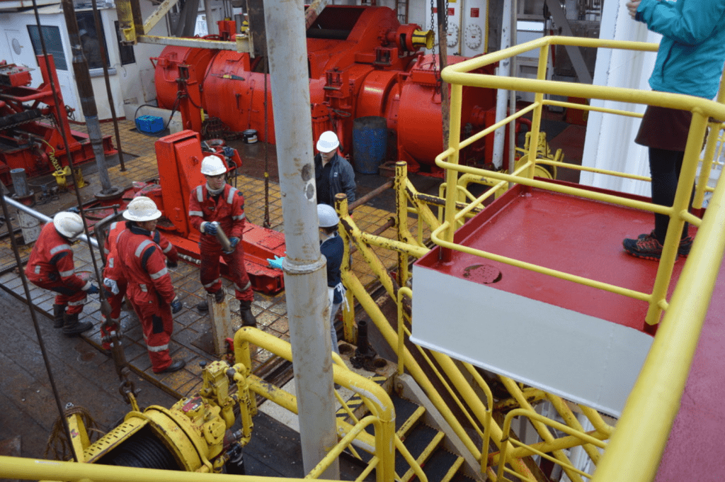 A driller in red coveralls hands a small metal tube, the core catcher, to a lab tech. There are several other people standing with them on the rig floor.