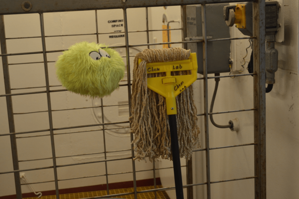 A fuzzy green plushie, Little Cthulhu, sitting on a rack next to a mop head. The mop head looks almost like a person's long hair hanging down. LC is positioned so it looks like it's looking at the mop head.
