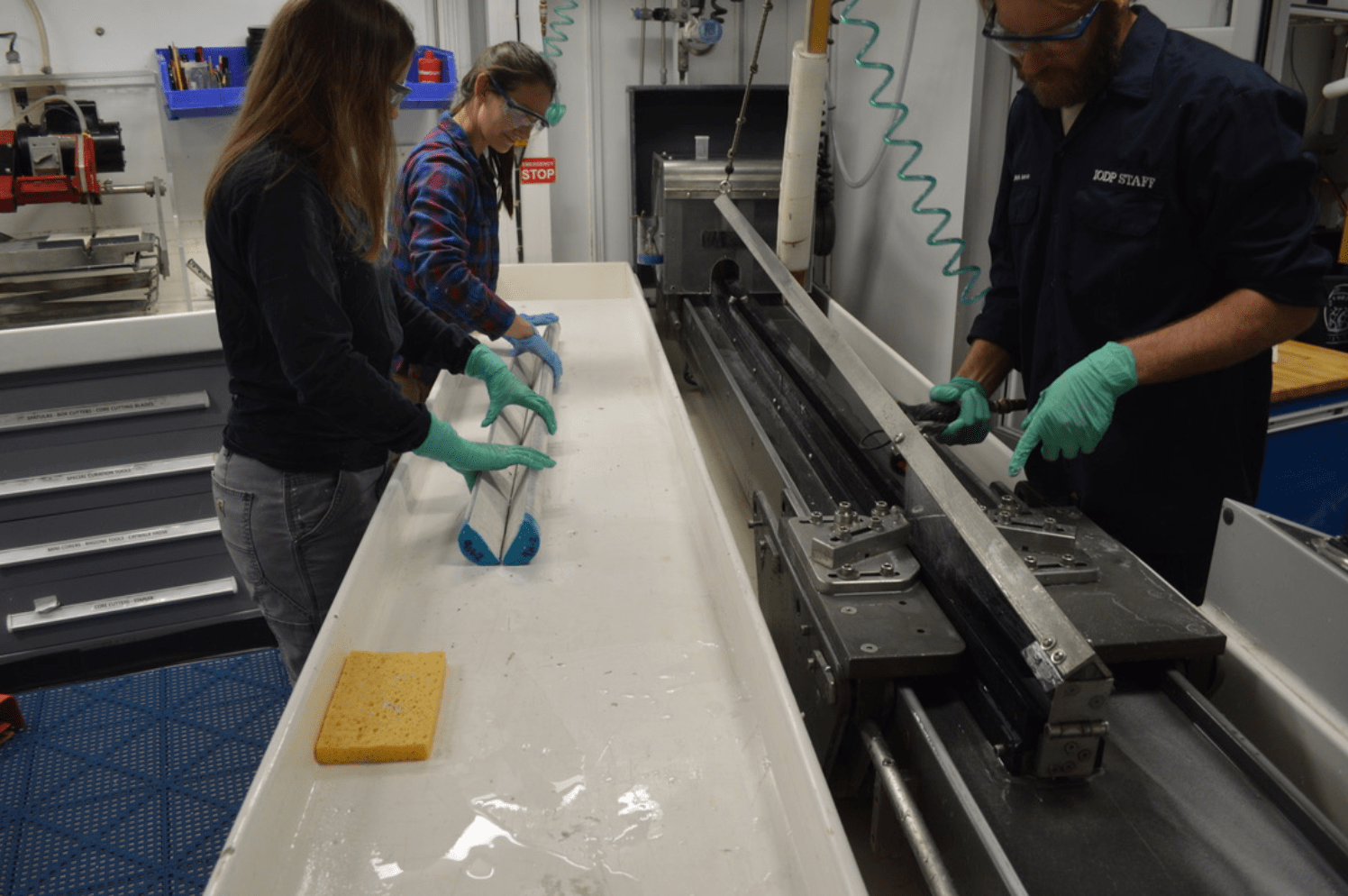 Three technicians in the core splitting room. One is spraying the core cutter with a hose. The other two are holding a core that has just been split, and you can see the insides of the core.