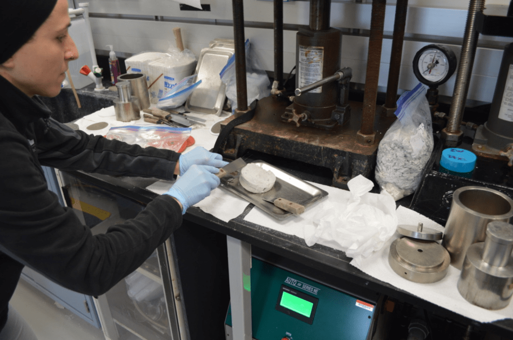 A scientist is touching a squeeze cake with a metal spatula while it sits on a plate. The squeeze cake is a thick disc of sediment, about palm sized. There are several large grey instruments in the background - hydraulic squeezers.