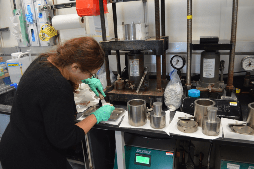 A scientist manipulates a squeeze cake using two metal spatulas. Her back is to the camera and she is working intently. She is surrounded by hydraulic squeezers and large metal implements.