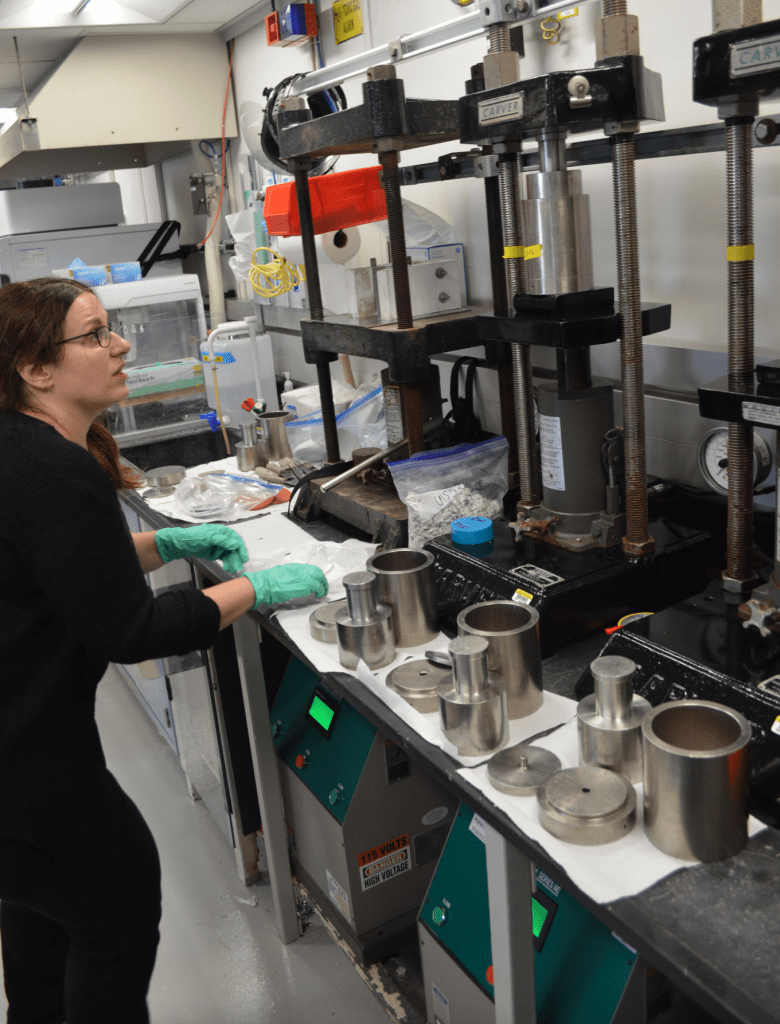 A scientist, Eleni, is looking up intently at the hydraulic squeezer. There is a metal cylinder and a plunger in the jaws of the squeezer.