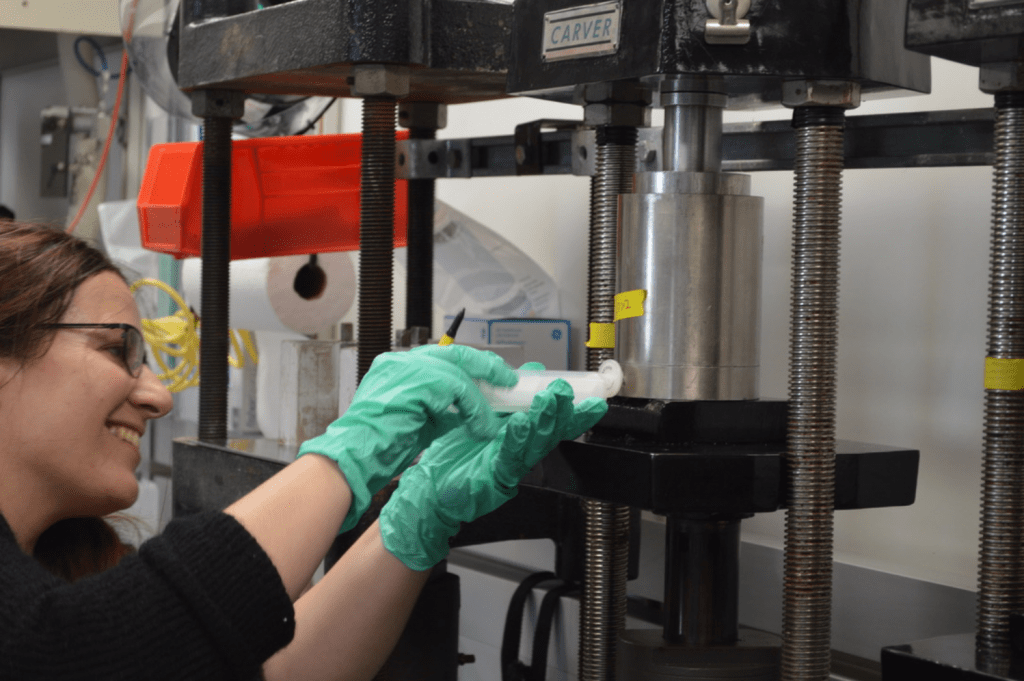 Eleni is holding a syringe up to a hole in the bottom of the squeeze cake cylinder. She is looking at the squeezer and smiling.