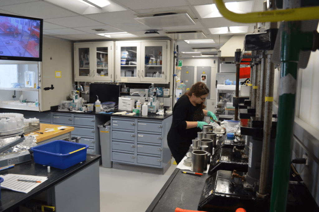 A wide shot of the lab. Eleni is standing at a lab bench lined with hydraulic squeezers. Behind her is a lab bench full of machines with glass tubes sticking out of the tops. There is a television mounted to the wall, and it is showing a grainy grey and red image of the rig floor.
