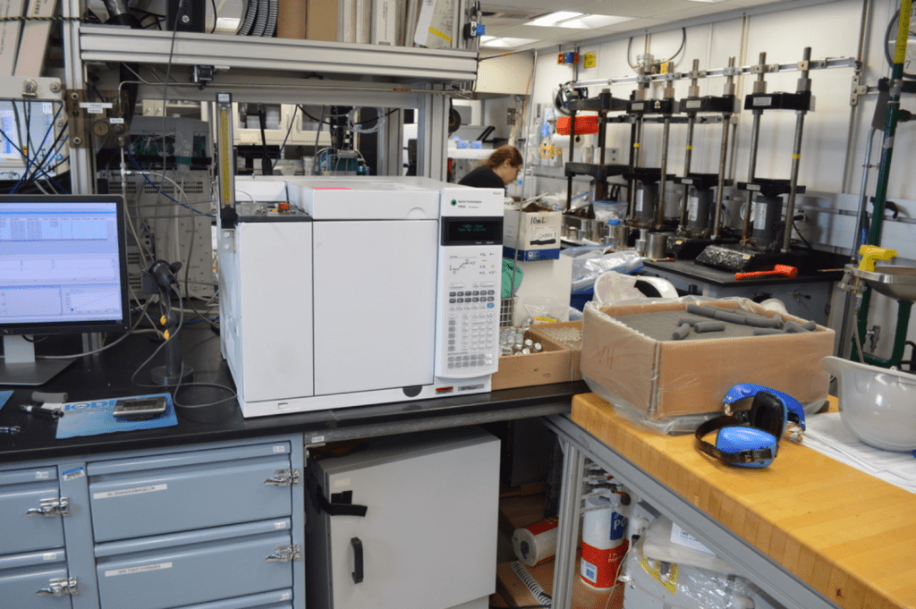 A large (mini-fridge sized) white instrument shaped like a box, sitting on a lab bench. There is a computer next to it and several boxes of glass vials and other chemistry equipment scattered around the lab.