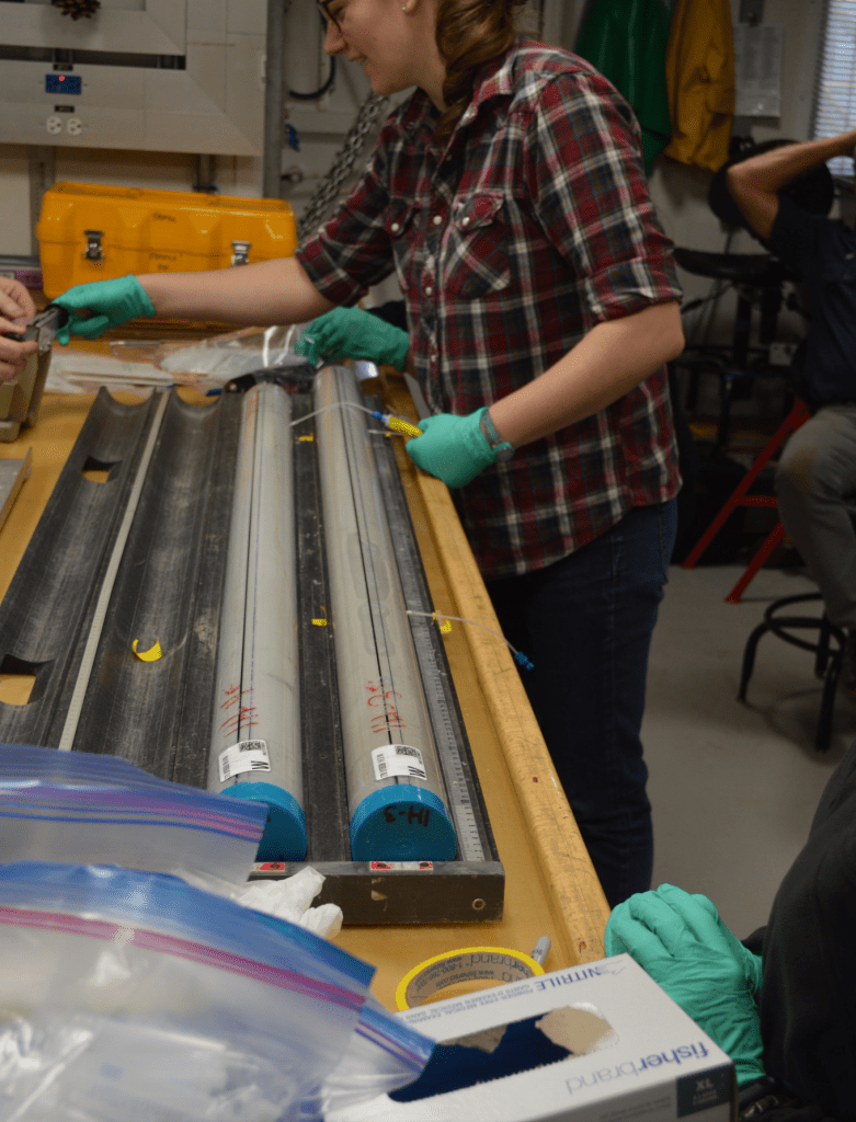 A scientist, Ann, standing at a wooden lab bench. There are two cores in front of her on the bench. Each has a tube in the plastic core liner with a syringe attached to it. Ann is holding one of the syringes and talking to someone off-frame.