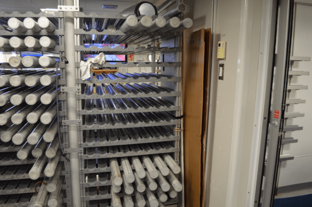 A tall rack with several white core sections resting on the shelves.