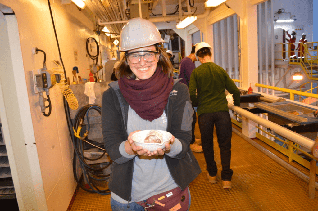 A scientist looking at the camera and smiling brightly. She is wearing a hard hat and safety glasses, and she is holding a sediment sample in a ceramic bowl with both hands.