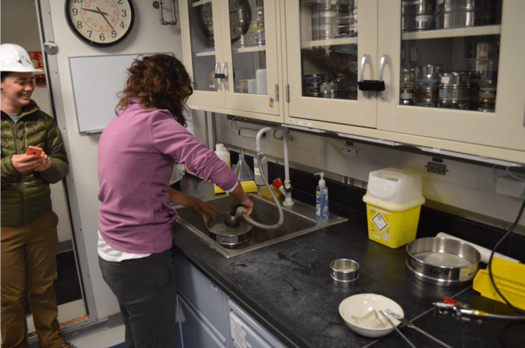 A scientist stands at a lab bench with her back to the camera. She is using a sprayer attachment on a sink to spray the sediment inside a sieve. Another person stands nearby, looking at Flavia and smiling.
