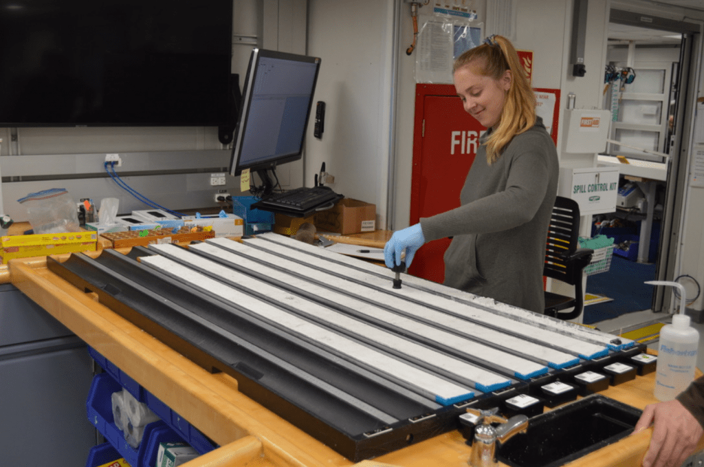 A scientist, Gabby Kitch, stands at the working table with several section halves of core. She is smiling and pressing a small black device, a shear strength tester, into a core. The cores are very light grey in color.
