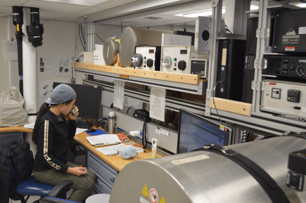 A scientist, Wendy Zhang, sits at a table lined with lab equipment and computer screens. She is turned away from the camera and is sipping coffee out of a small cup. The lab bench is partially obscured by a large, silver cylinder - a magnetometer.