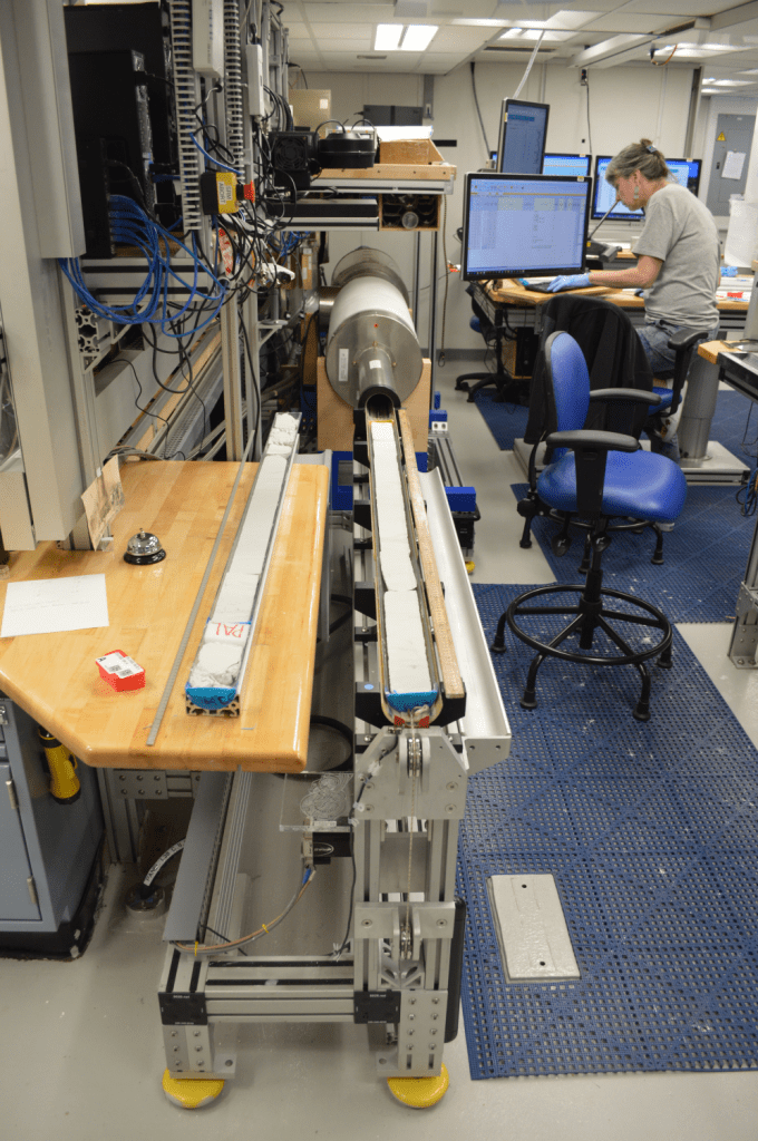 A photo of the superconducting rock magnetometer, or SRM. The SRM is a long metal cylinder with a hole in one end. A section half of core is lined up with the hole on a track. In the background a scientist, Ingrid Hendy, is working at a computer.